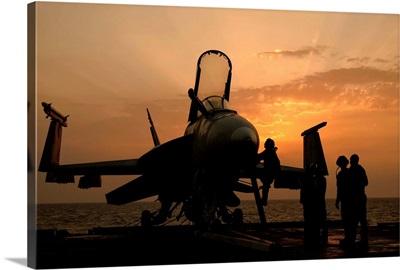 An F/18C Hornet aboard USS George H.W. Bush during sunrise