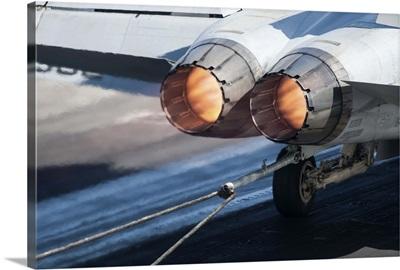 An F/A-18C Hornet catches an arresting gear wire