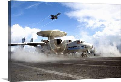 An F/A-18C Hornet flies overhead as an E-2C Hawkeye prepares to launch