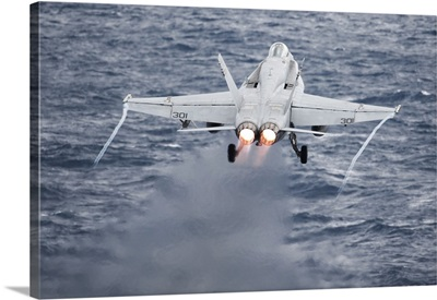 An F/A-18C Hornet launches from the flight deck of USS Harry S. Truman