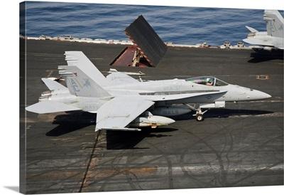 An F/A-18C Hornet sits ready on the flight deck of USS Harry S. Truman