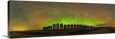 Aurora borealis behind grain bins on a country road in Alberta, Canada