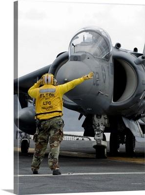 Aviation Boatswain's Mate directs the pilot of an AV-8B Harrier II