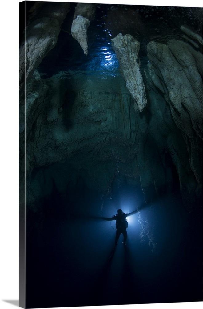 Backlit diver in Chandelier Cave with large stalactites