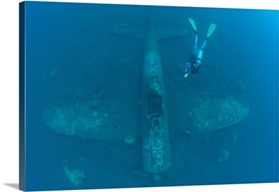 Diver explores the wreck of a Mitsubishi Zero fighter plane