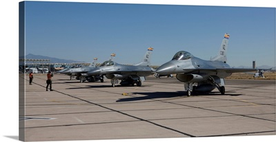 F-16s line up at the end of the runway for preflight checks