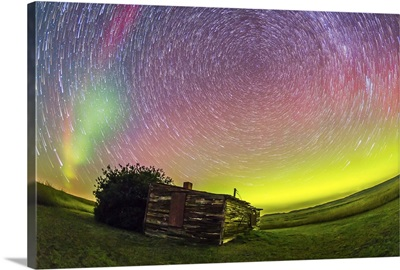 Fish-eye lens composite of aurora and circumpolar star trails above ranch in Canada