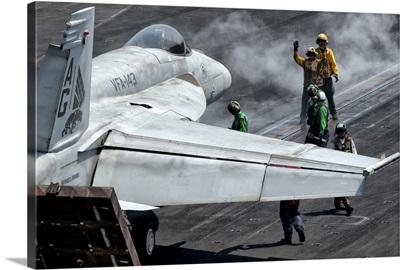 Flight deck crew position an F/A-18E Super Hornet into launch position