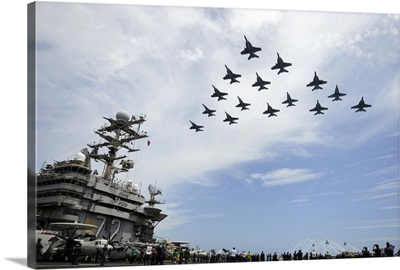 Helicopters and jets fly in formation above flight deck of USS Abraham Lincoln