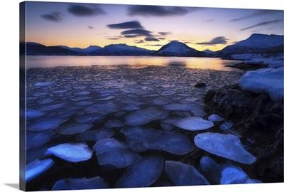Ice flakes drifting against the sunset in Tjeldsundet strait, Troms County, Norway