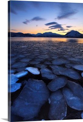 Ice flakes drifting towards the mountains on Tjeldoya Island, Norway