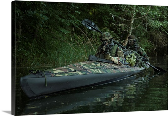 navy seals navigate the waters in a folding kayak during jungle