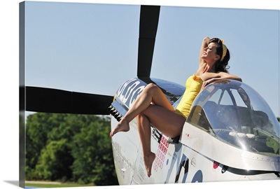 Retro pin-up girl sitting outside the cockpit of a P-51 Mustang