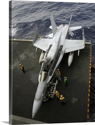 Sailors move an F/A-18C Hornet into the hangar bay