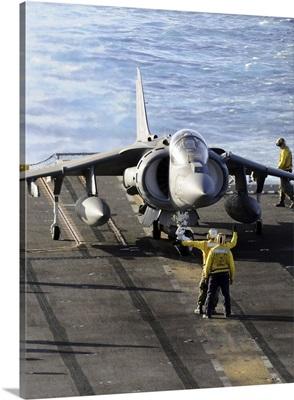 Sailors prepare to launch an AV-8B Harrier during flight operations aboard USS Peleliu