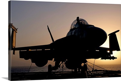 Silhouette of a US Navy F/A-18E Super Hornet on the flight deck of USS Nimitz