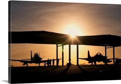 Two Embraer A-29 Super Tucano aircraft parked in the hangar at Natal Air Force Base