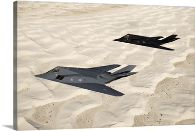 Two F-117 Nighthawk stealth fighters fly over White Sands National Monument