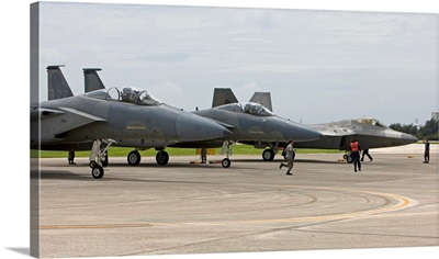 Two F-15s and an F-22 raptor parked on the runway at Kadena Air Base, Japan