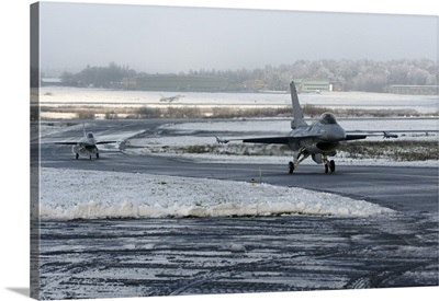 Two F-16 Fighting Falcons taxi down the runway in Florennes, Belgium