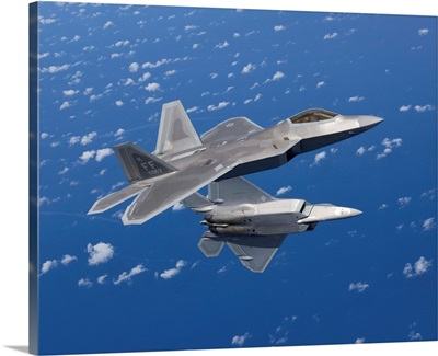 Two F-22 Raptors maneuver while flying a training mission over Japan
