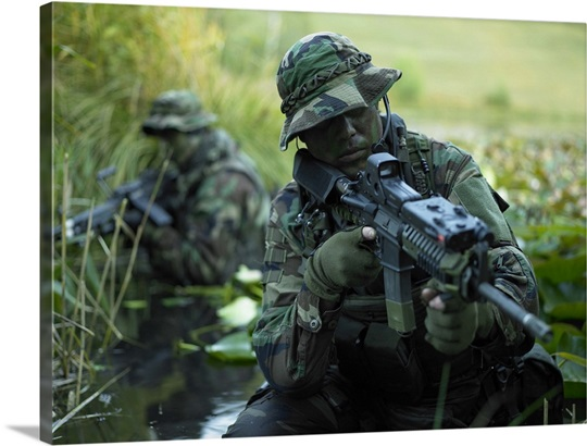 us navy seals cross through a stream during combat