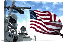 USS Cowpens flies a large American flag during a live fire weapons shoot
