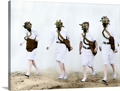 U.S. Army nurses advance through a cloud of smoke in a gas mask drill during training