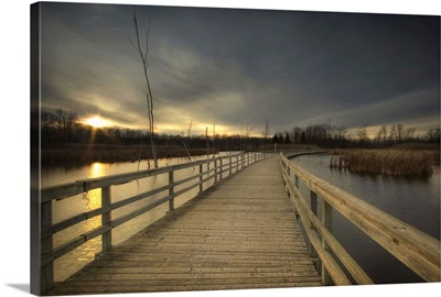 A wooden jetty across a lake at sunset
