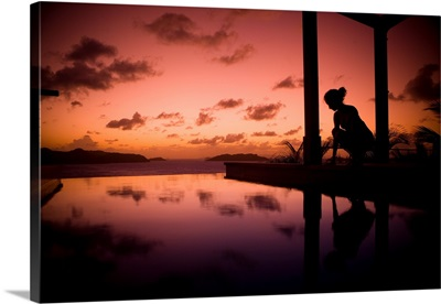 A young girl admires the reflections of a sunset in a pool