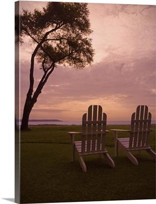 Adirondack chairs sit on a grassy field at sunset