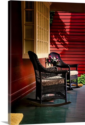 An American front porch with wooden boarding and two whicker rocking chairs