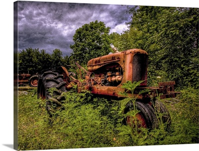 An old red 1950's tractor left to decay in a field