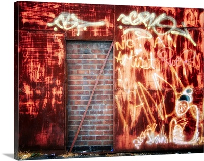 Filled in derelict door with red brickwork and graffiti