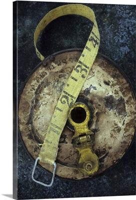 Groundsmans measuring tape in well worn metal case lying on metal sheet II