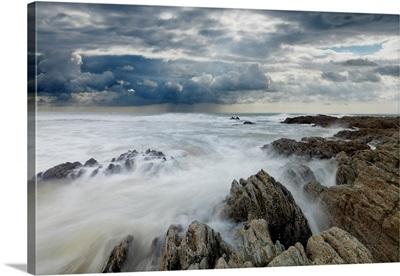 Jagged rocks on coastline with white surf under grey storm clouds