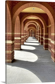 Looking along a line of brick archways with sunlight and shade