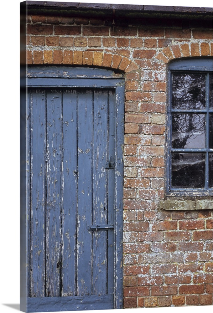 Old orange brick stable block with blue painted wooden door and ...