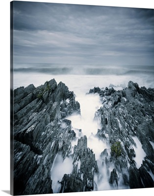 Rough sea with surf and rugged rocks under stormy sky