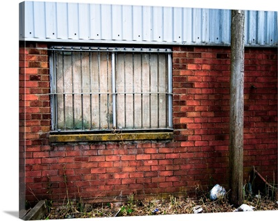 Side of derelict buidling with window and lampost