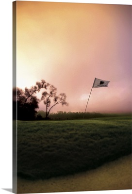 The flag pole on a golf course bends and shakes in the wind