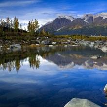 Bonanza Ridge and its reflection on a waterhole by the toe of Kennicott Glacier