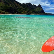 Hawaii, Kauai, Haena Beach, Red Surfboard Floating In Shallow Ocean