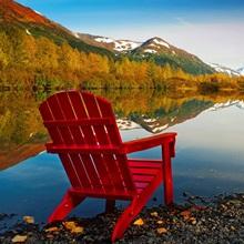 Red Adirondak chair along lakeshore, Alaska