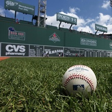 A Major League Baseball in the grass in front of the Green Monster in Fenway park