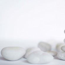 Stack of white pebbles on white background.