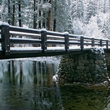 A snow-covered footbridge spanning the Merced River, Yosemite National Park, California