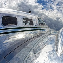 Clouds and sky reflecting off the shiny silver surface of an airplane