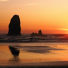 The sun sets over sea stacks at Cannon Beach, Ecola State Park, Oregon