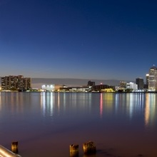 Buildings in a city lit up at dusk, Detroit River, Detroit, Michigan,